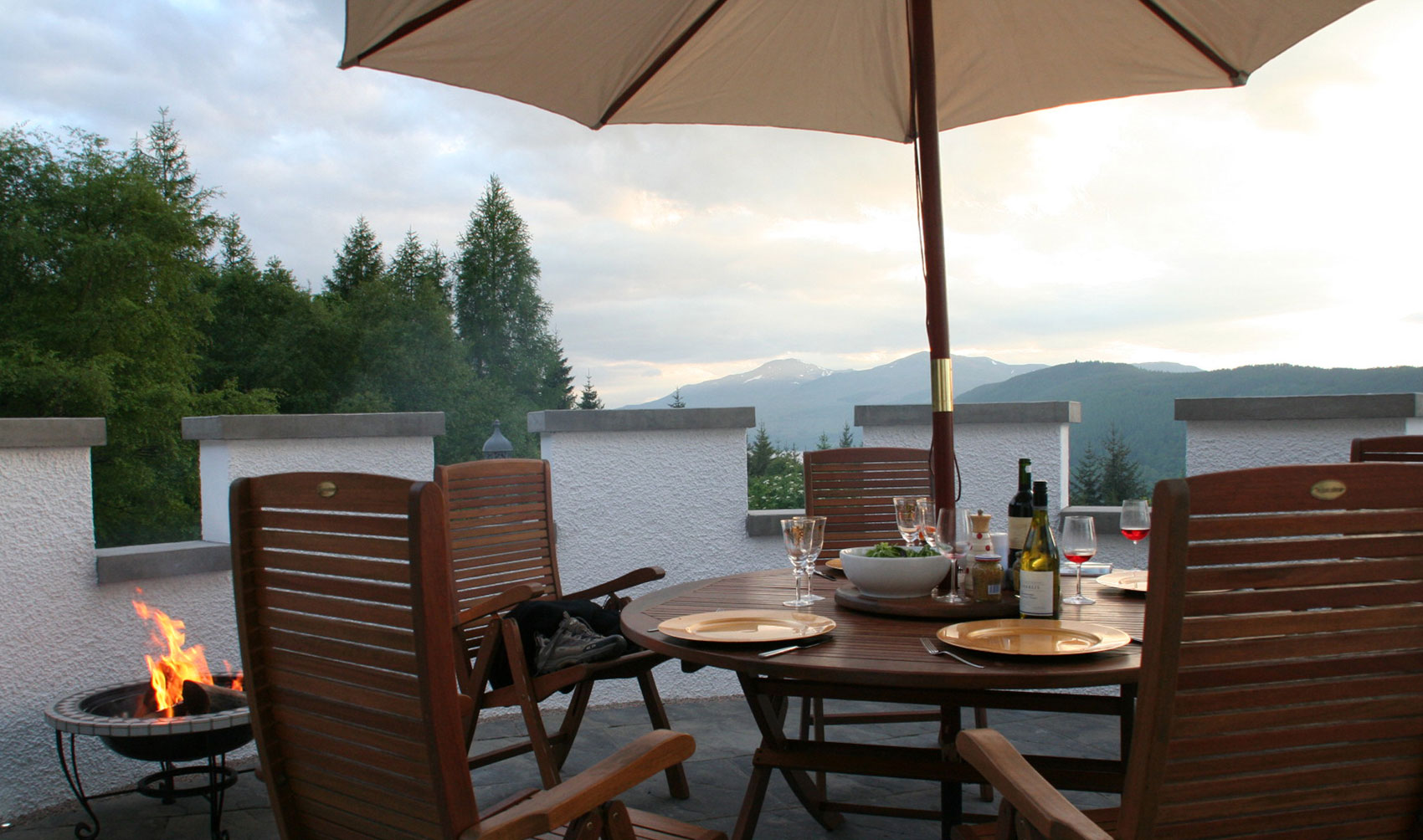 rooftop terrace with table chairs and parasol overlooking montains